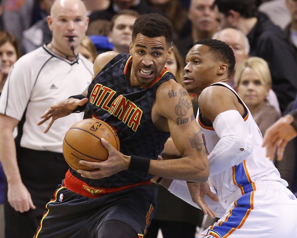 Atlanta Hawks forward Thabo Sefolosha, left, drives around Oklahoma City Thunder guard Russell Westbrook, right, in the first half of a...