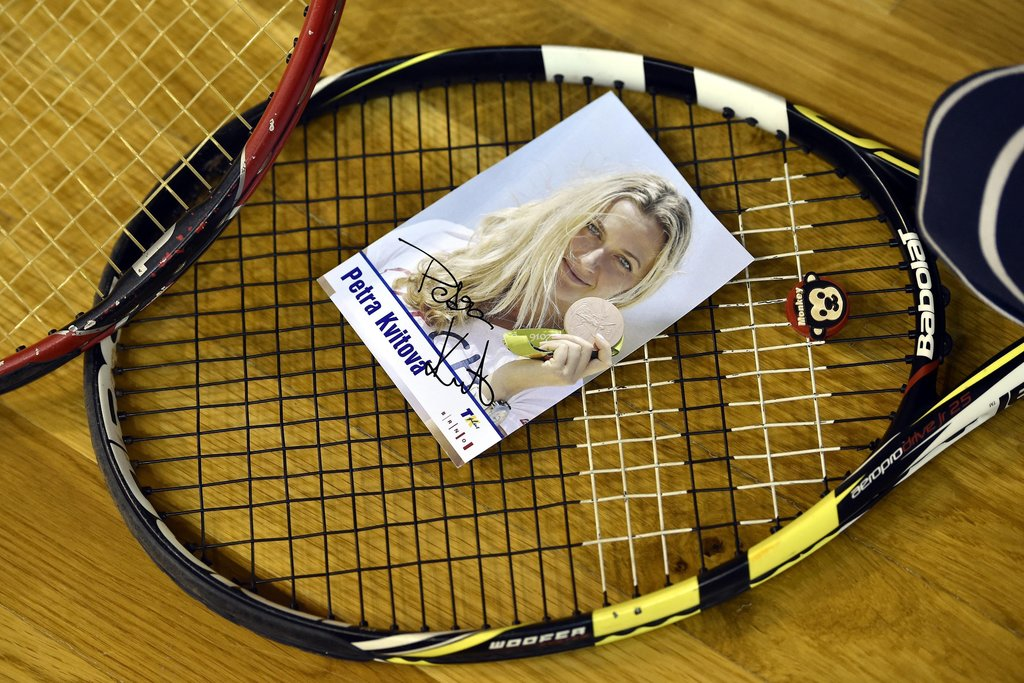 A photograph of Czech tennis player Petra Kvitova lies on a tennis racket during a charity tennis exhibition in Brno, Tuesday, Dec. 20,...