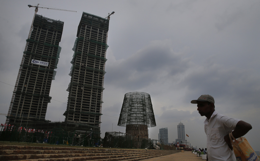 In this Monday, Dec. 19, 2016 photo, a Sri Lankan man stands near the construction site of an enormous, artificial Christmas tree, cent...