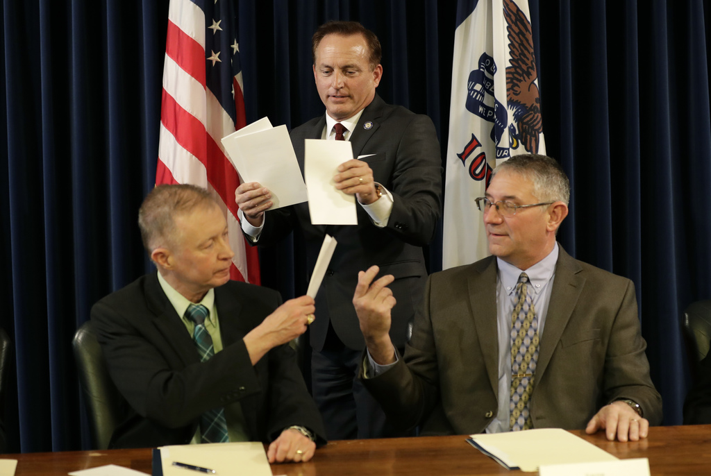 Iowa Sec. of State Paul Pate, center, collects ballots from Iowa electors Alan Braun, of Norwalk, Iowa, left, and Don Kass, of Remsen, ...