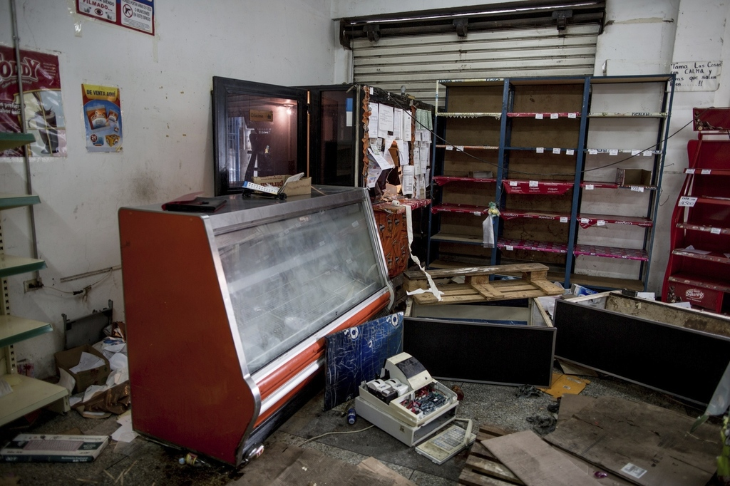 A grocery store is left in disarray after it was looted by demonstrators the night before, in Ciudad Bolivar, Venezuela, Monday, Dec. 1...