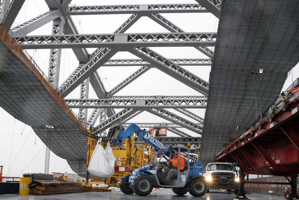 FILE - In this Nov. 15, 2016, file photo, a worker lifts materials as construction continues on the new roadway deck of the Bayonne Bri...