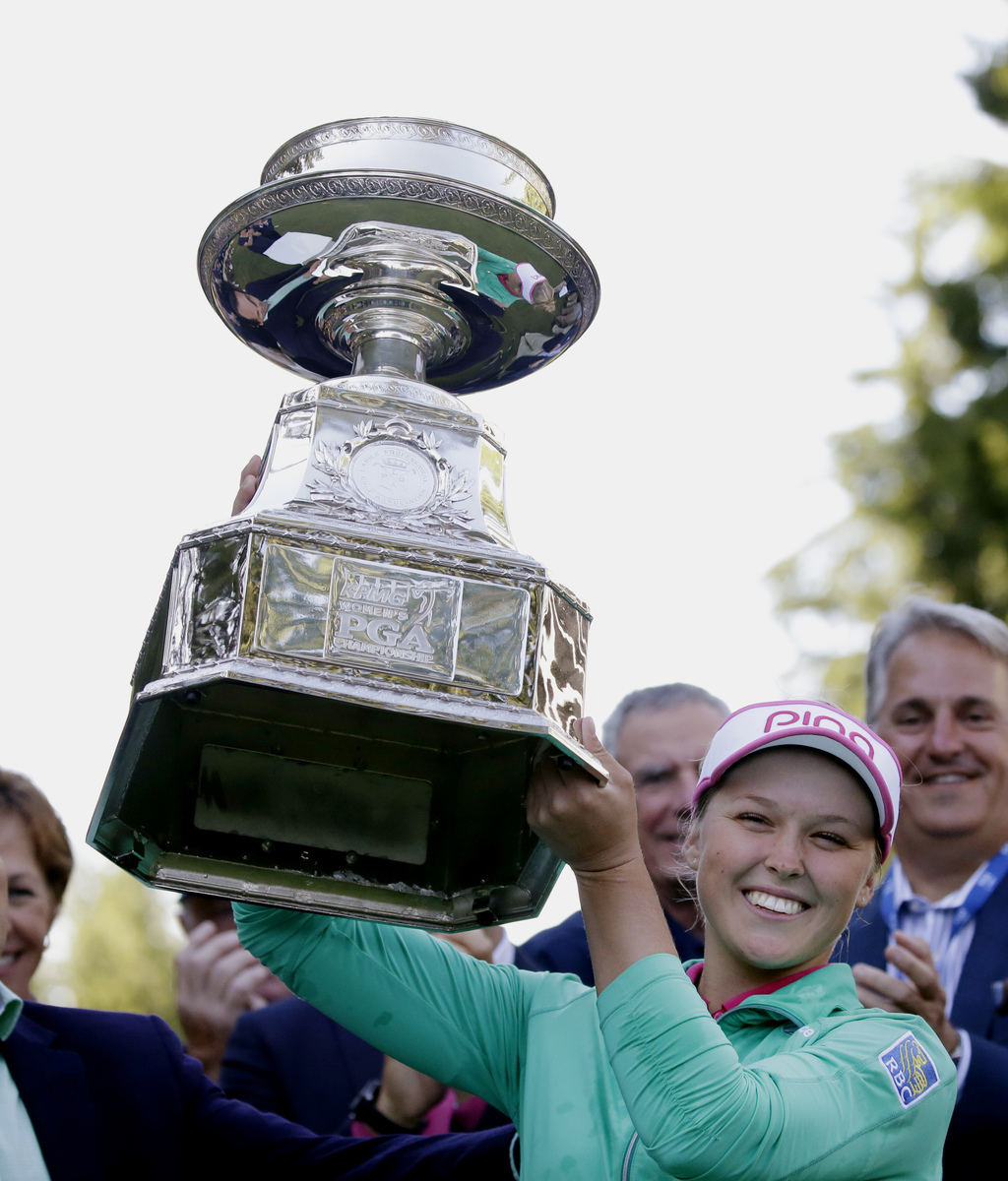 FILE - In this June 12, 2016, file photo, Brooke Henderson, of Canada, lifts the championship trophy after winning the Women's PGA Cham...
