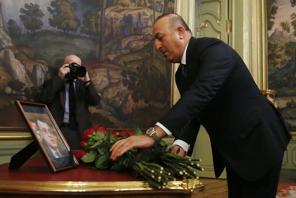 Turkey's Foreign Minister Mevlut Cavusoglu offers flowers in memory of Russian Ambassador to Turkey Andrei Karlov, who was fatally shot...