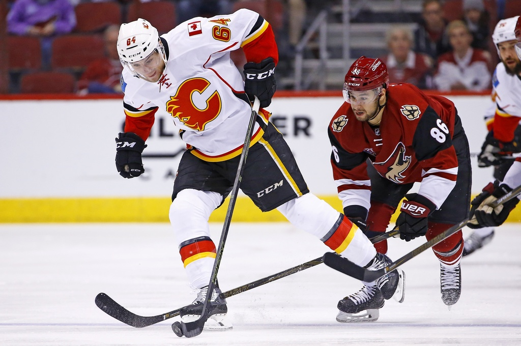 Calgary Flames right wing Garnet Hathaway (64) beats Arizona Coyotes right wing Josh Jooris (86) to the puck during the first period of...