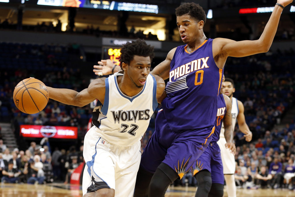Minnesota Timberwolves' Andrew Wiggins drives around Phoenix Suns forward Marquese Chriss during the second half of an NBA basketball g...