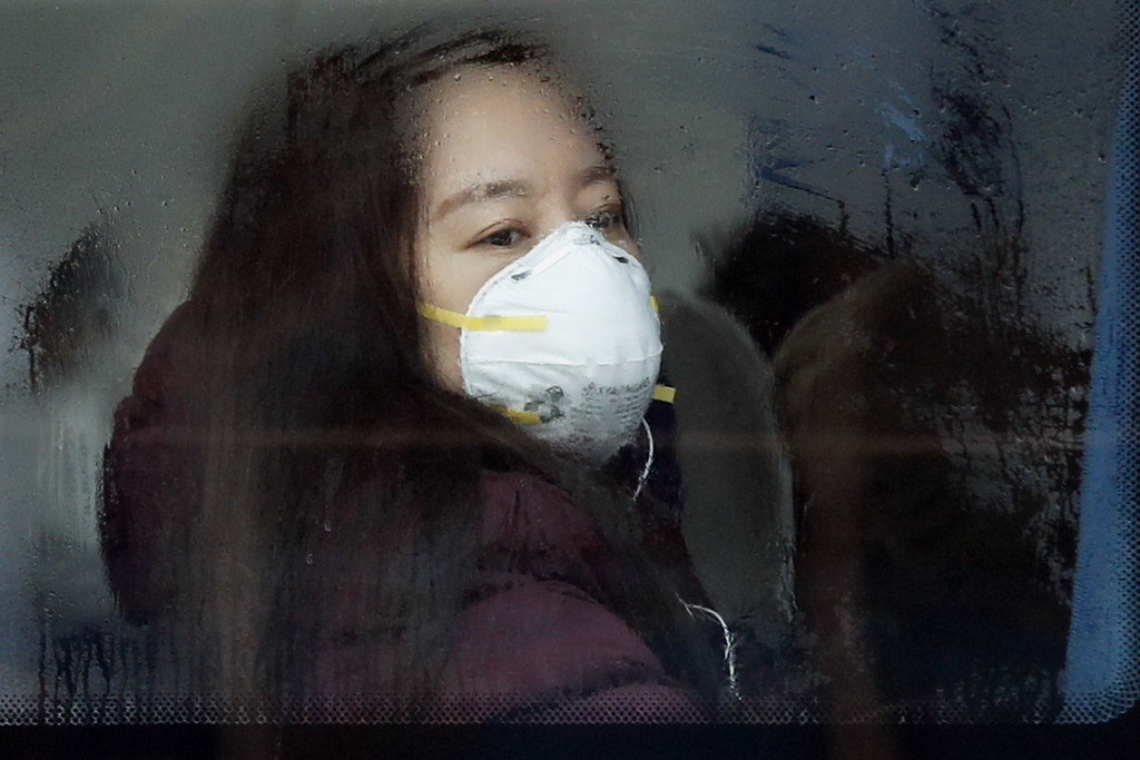 CORRECTS DAY OF WEEK - A woman wearing a mask for protection against air pollution looks out from a bus in Beijing as the capital of Ch...