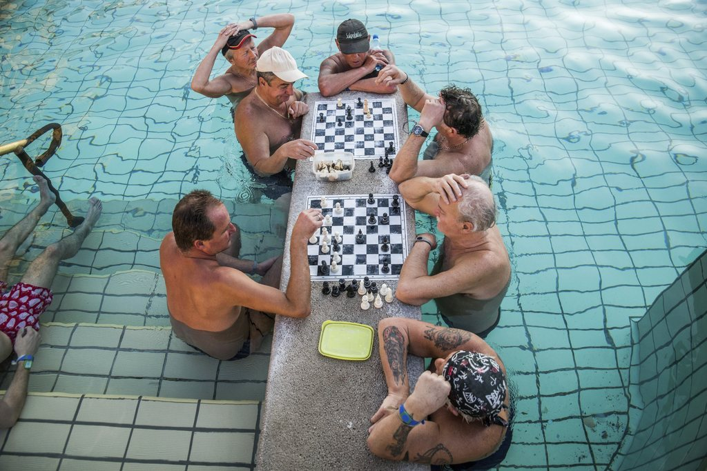 FILE - In this March 21, 2016 file photo visitors play chess in a pool of Szechenyi Thermal Bath and Swimming Pool in Budapest, Hungary...
