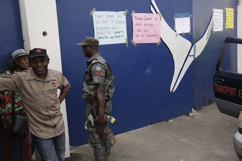 A police officer stand guards at the entrance of Arik Air's office during a protest by union and staff in Lagos, Nigeria, Tuesday, Dec....