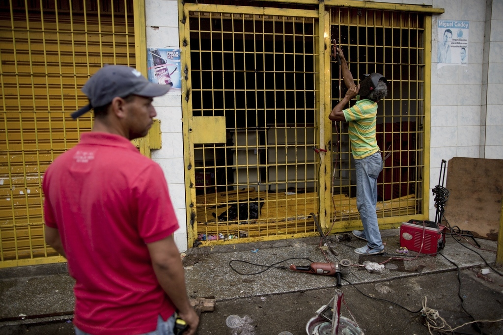 A store owner repairs the security gate at the entrance to his grocery store looted by demonstrators the night before, in Ciudad Boliva...