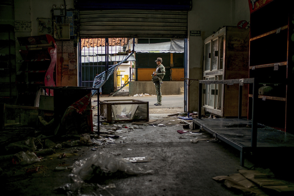 A Bolivarian National Guard officer stands guard outside of a grocery store looted by demonstrators the night before, in Ciudad Bolivar...