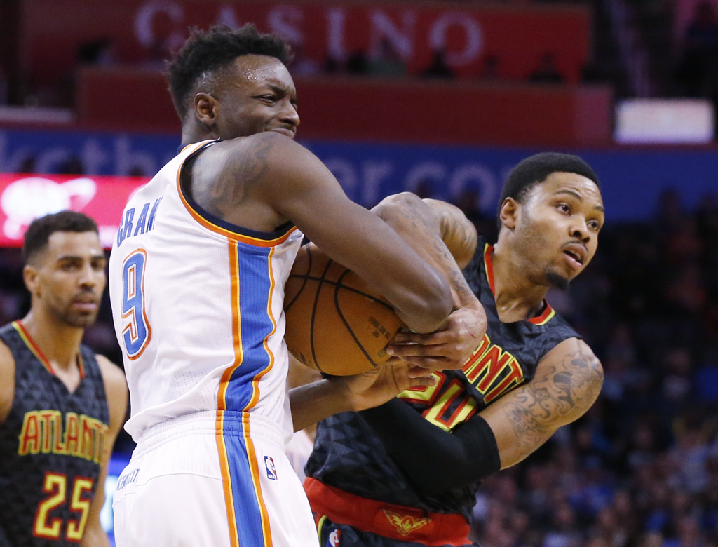 Oklahoma City Thunder forward Jerami Grant, left, and Atlanta Hawks forward Kent Bazemore, right, look to the referee as he blows a whi...