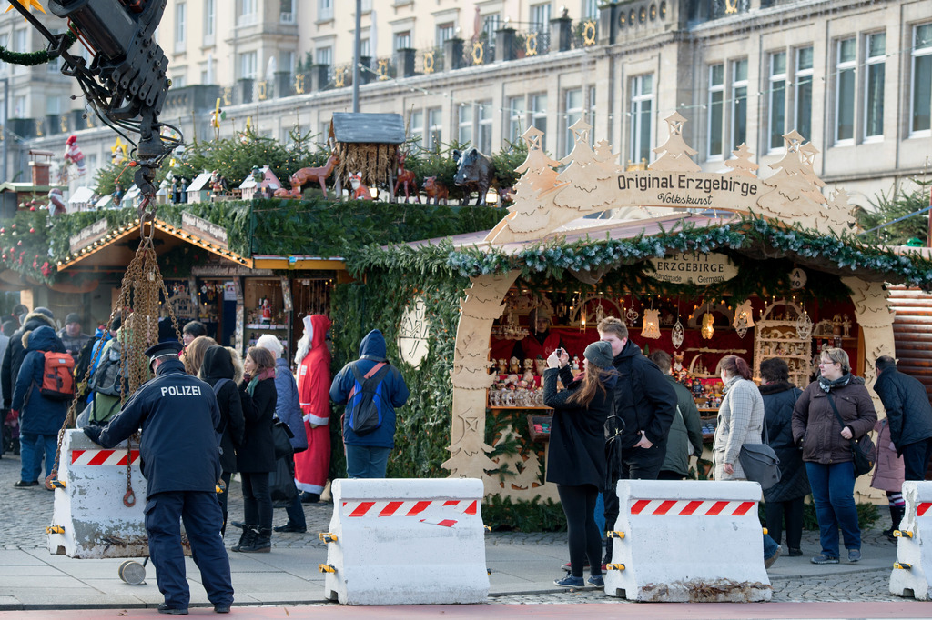 A police officer positions concrete blocks at an entrance to the Striezelmarkt Christmas market in Dresden, eastern Germany, Tuesday De...