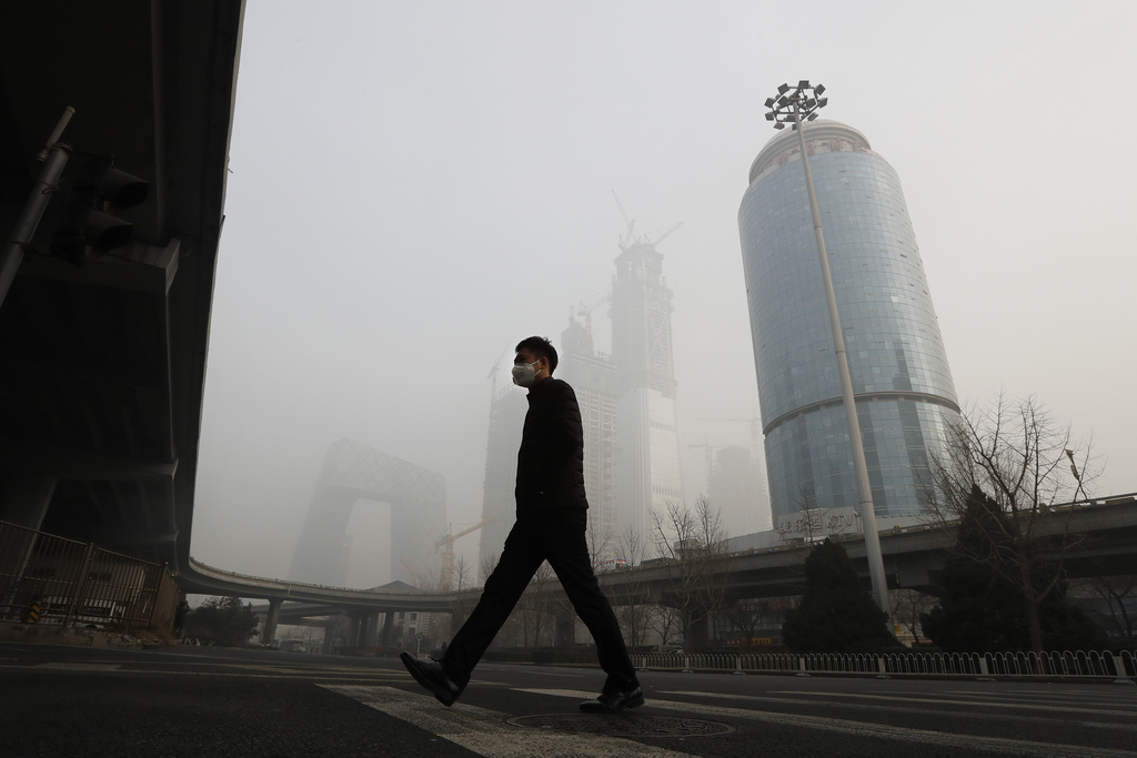 A man wearing a mask for protection against air pollution walks across a road in Beijing as the capital of China is shrouded by heavy s...