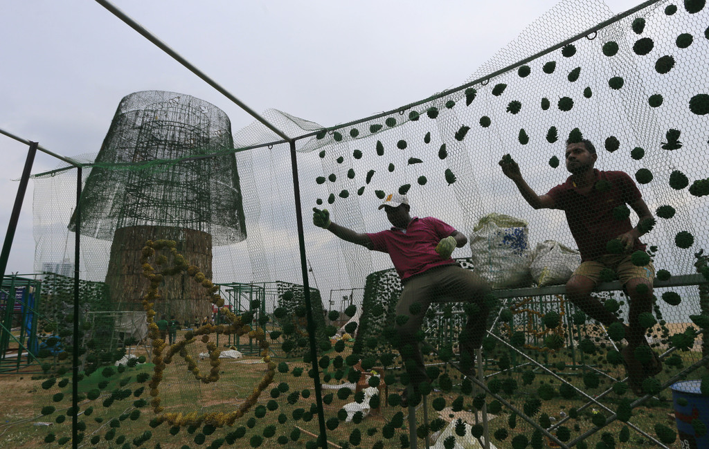 In this Monday, Dec. 19, 2016 photo, Sri Lankan port workers assemble decorations on frames as they try to build an enormous, artificia...