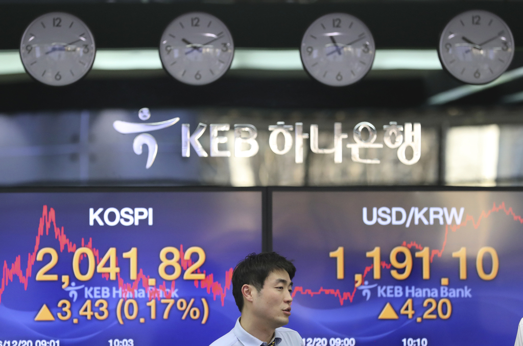 A currency trader walks by the screens showing the Korea Composite Stock Price Index (KOSPI), left, and the foreign exchange rate betwe...