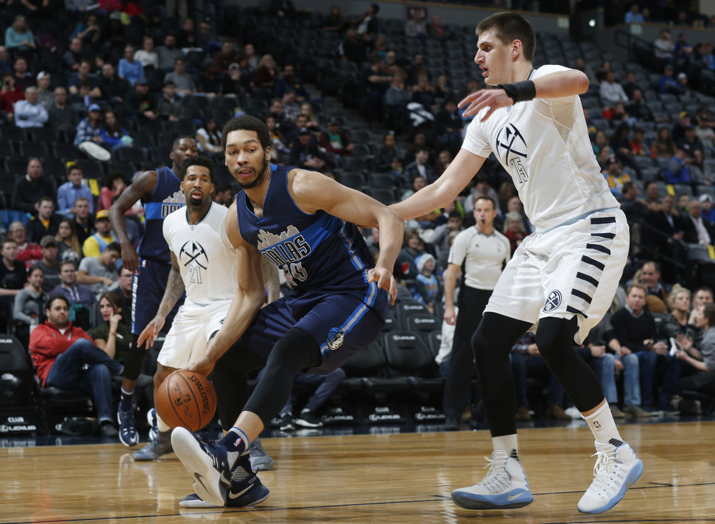 Dallas Mavericks center A.J. Hammons, center, picks up a loose ball between Denver Nuggets forwards Wilson Chandler, left, and Nikola J...
