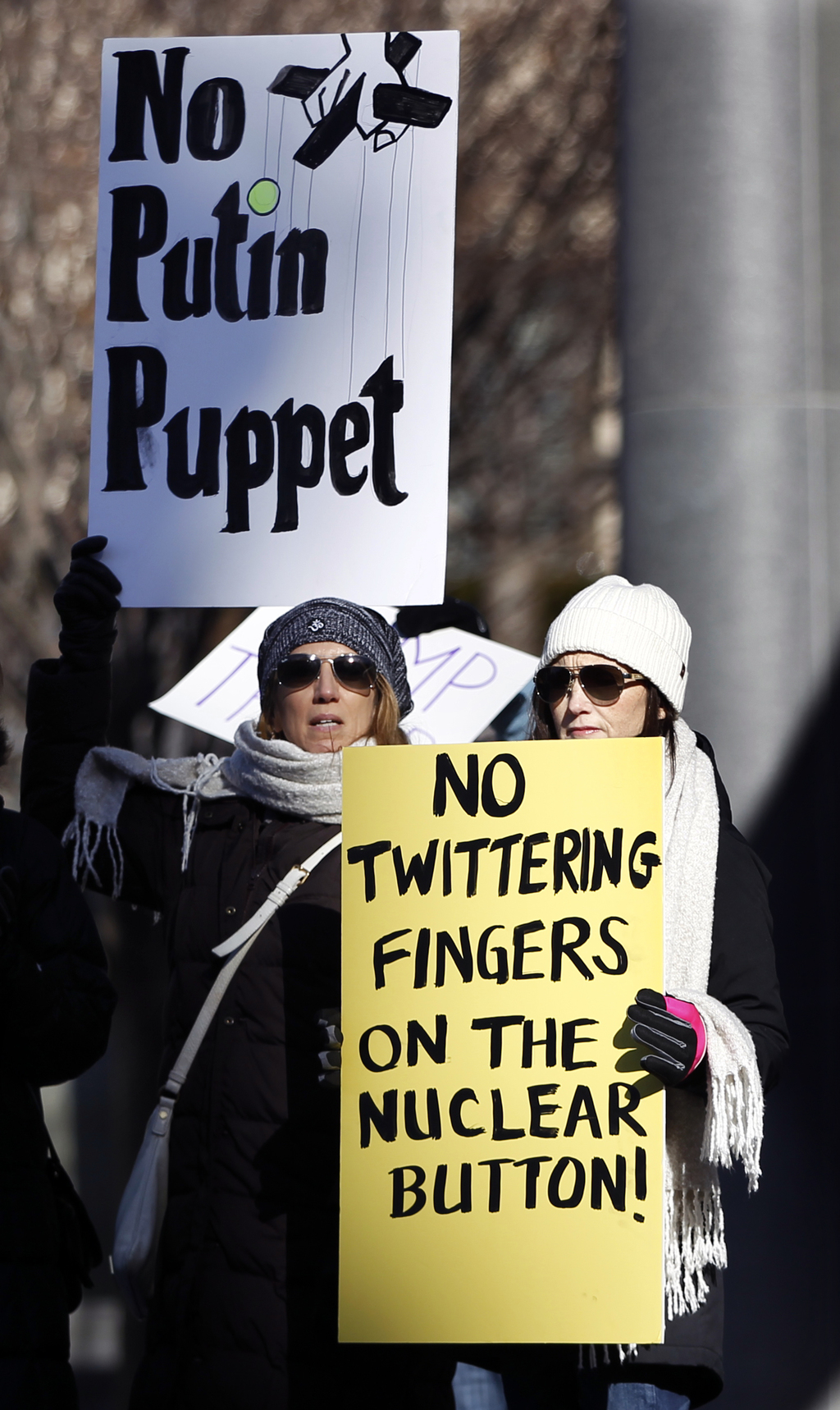 Protesters hold signs as they demonstrate against the election of Donald Trump in freezing temperatures near the Statehouse, ahead of N...