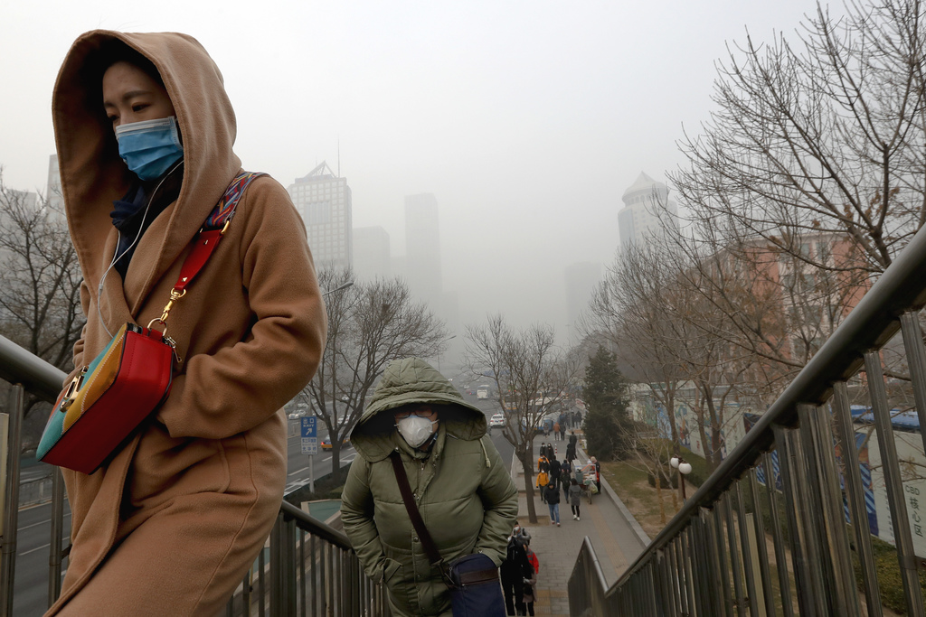 People wearing masks for protection against air pollution walk to a pedestrian overhead bridge in Beijing as the capital of China is sh...