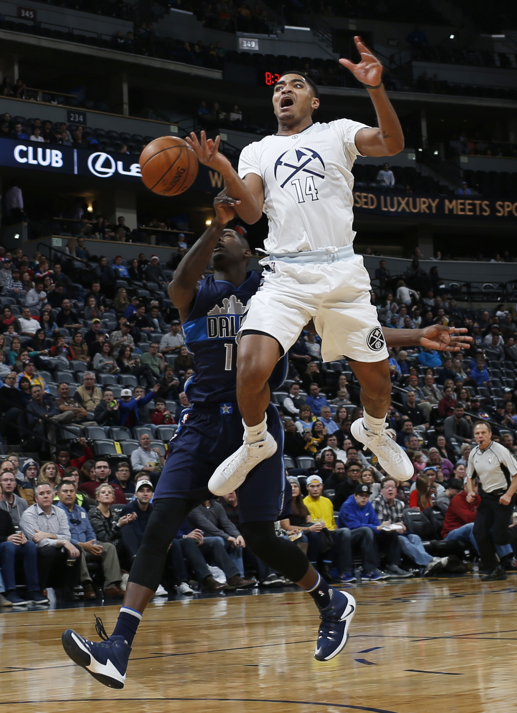 Denver Nuggets guard Gary Harris, front, is fouled as he goes up for a basket by Dallas Mavericks forward Dorian Finney-Smith in the se...