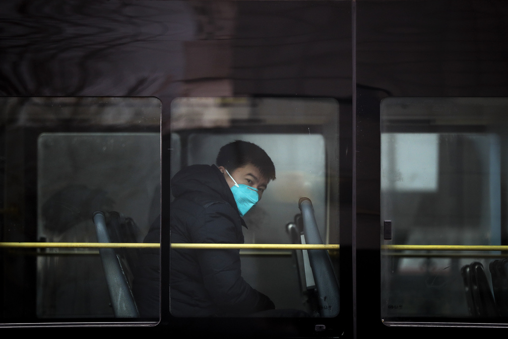A man wearing a mask for protection against air pollution looks out from a bus in Beijing as the capital of China is shrouded by heavy ...