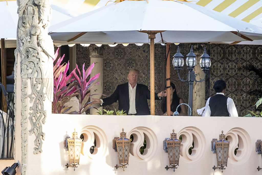 President-elect Donald Trump, center, speaks to an aide at Mar-a-Lago resort, in Palm Beach, Fla., Monday, Dec. 19, 2016. Trump is spen...
