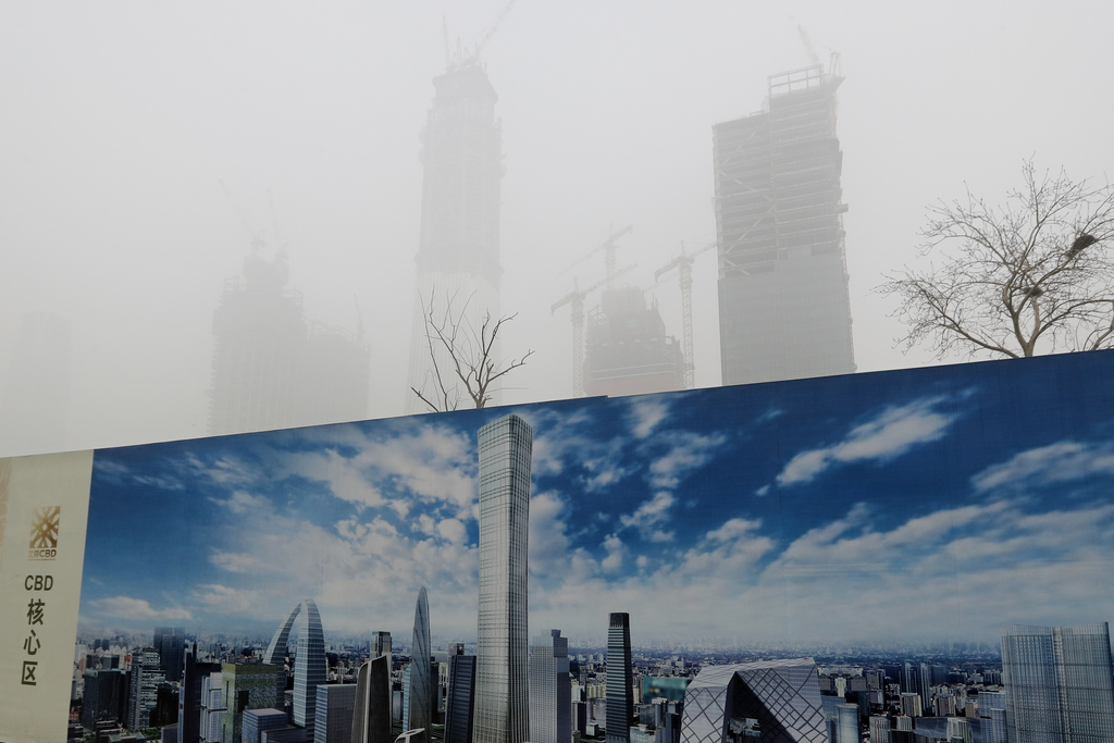 A construction site wall depicting the skyline of Beijing stands as the capital of China is shrouded by heavy smog on Tuesday, Dec. 20,...
