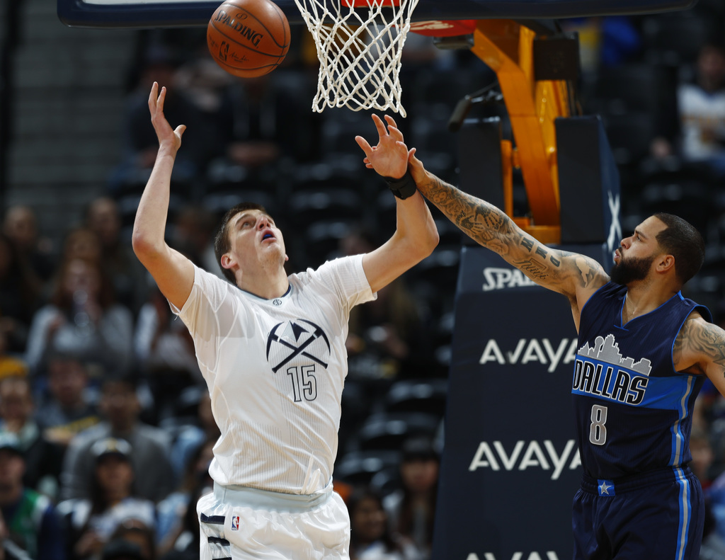 Denver Nuggets forward Nikola Jokic, left, of Serbia, looks toy rebound the ball as Dallas Mavericks guard Deron Williams defends in th...