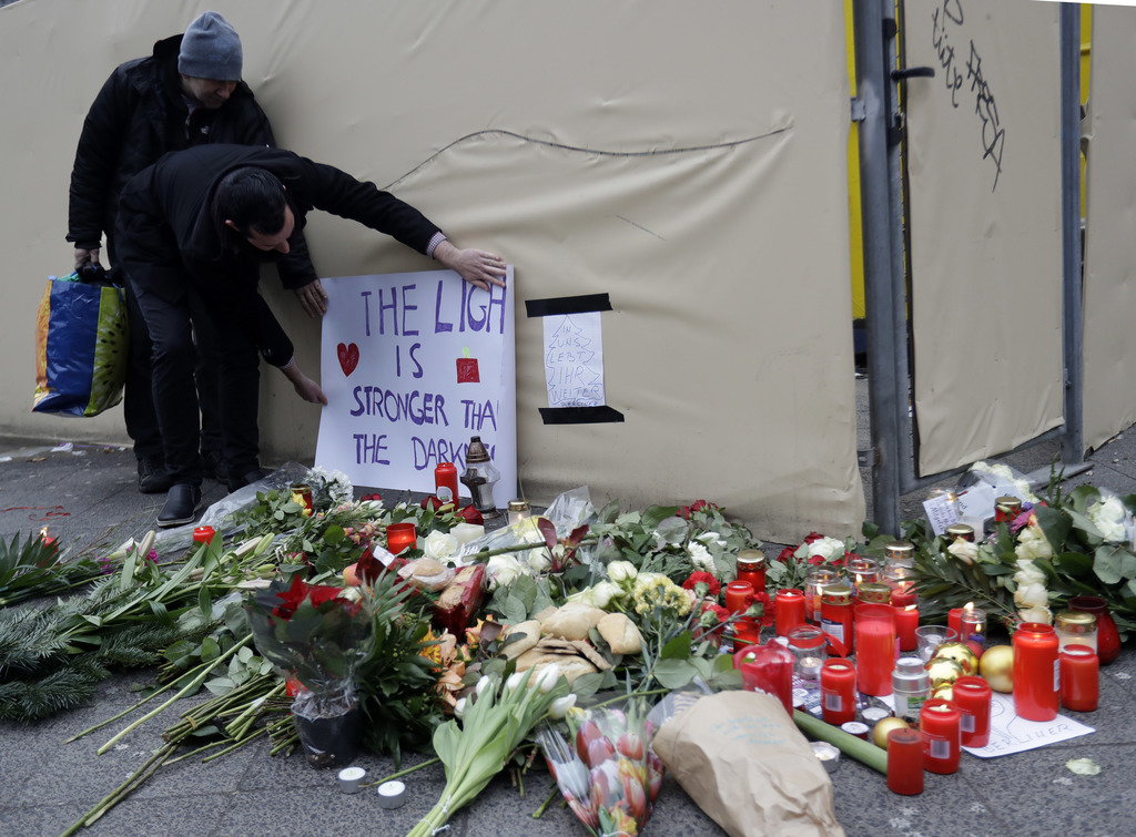 """A man attaches a poster """"The light is stronger than the darkness"""" in Berlin, Germany, Tuesday, Dec. 20, 2016, the day after a truck ran..."""