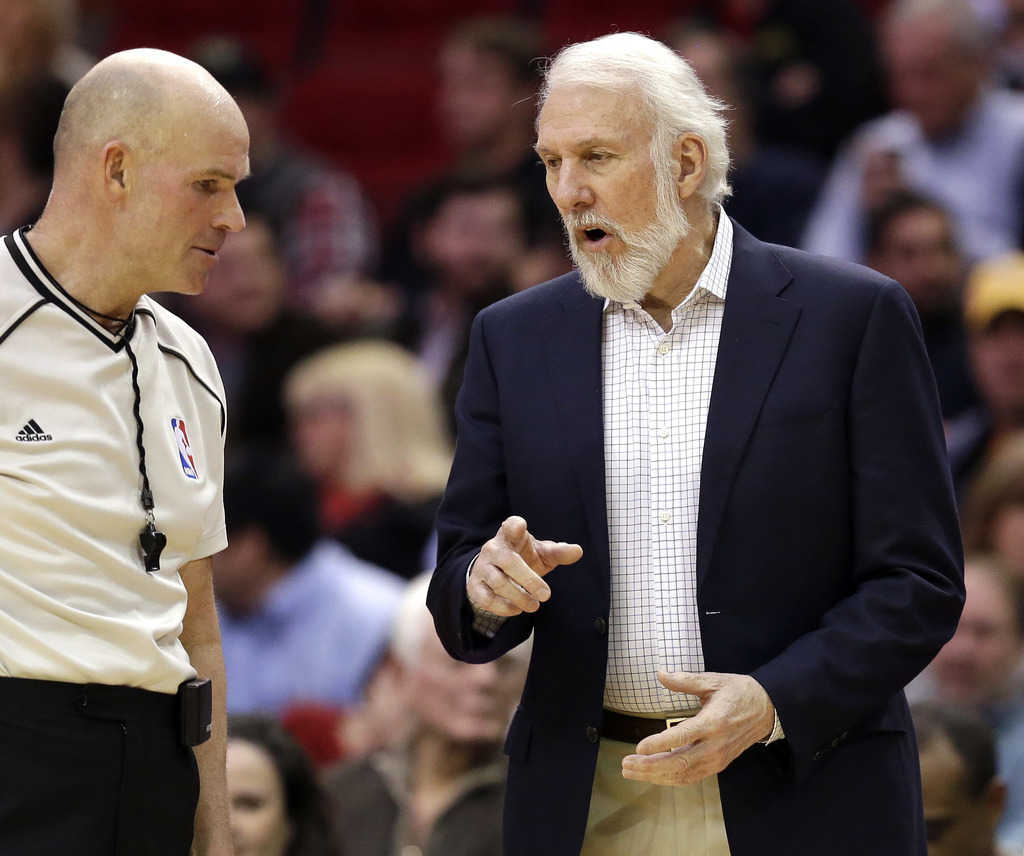 San Antonio Spurs coach Gregg Popovich, right, talks with referee Gary Zielinski during the first half of the team's NBA basketball gam...