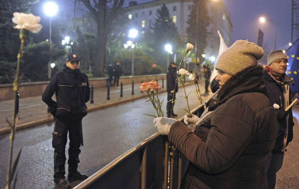 A woman puts flowers on a fence set up by the police to block access to the parliament, in Warsaw, Poland, Tuesday, Dec. 20, 2016. Alth...