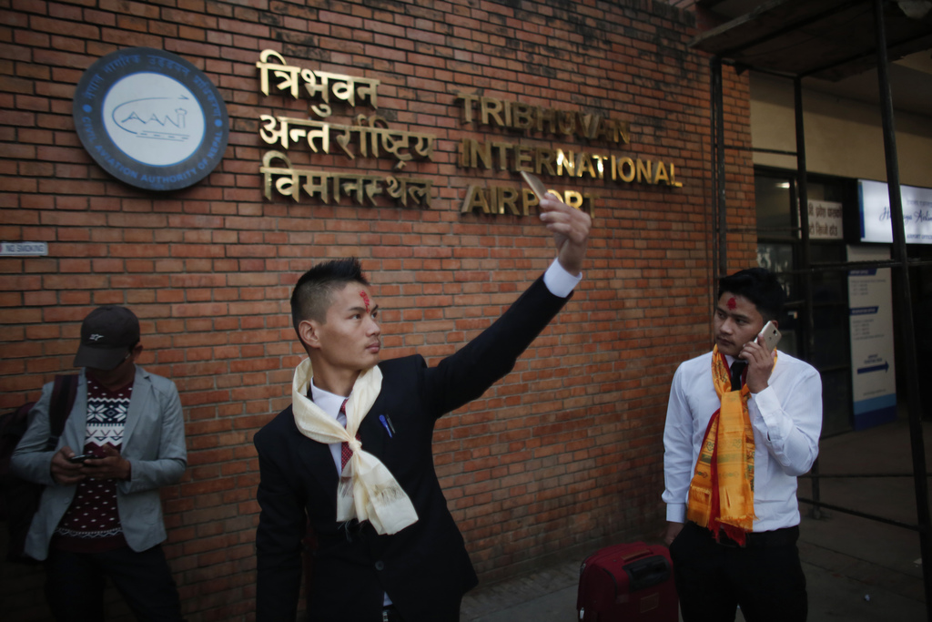 In this photo taken on Monday, Nov. 28, 2016, a Nepali Prem Bahadur Ale Magar, 23, takes a selfie while he waits for his flight to Mala...