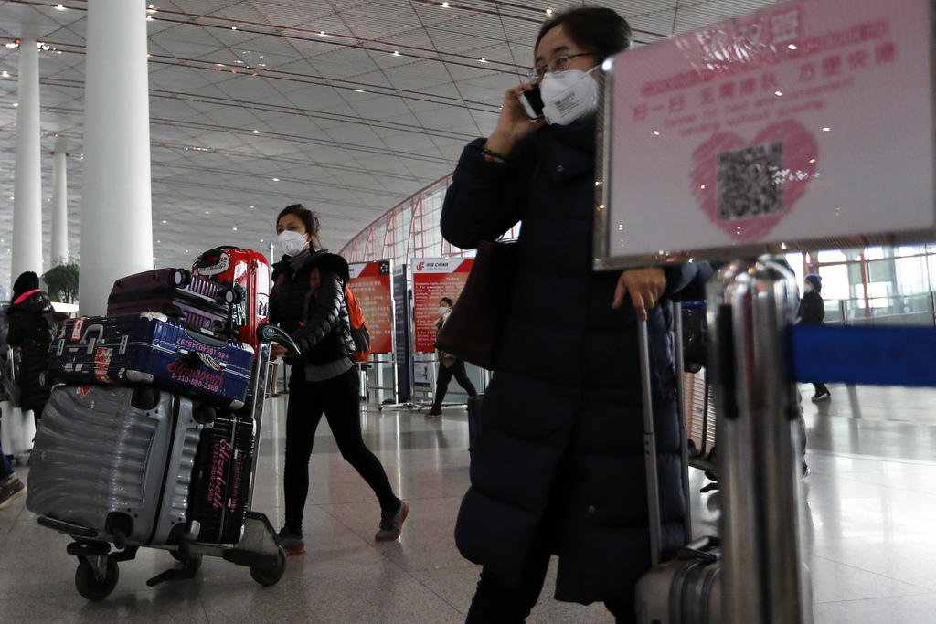 People wearing masks for protection against air pollution push their luggage at the Beijing Capital International Airport as the capita...