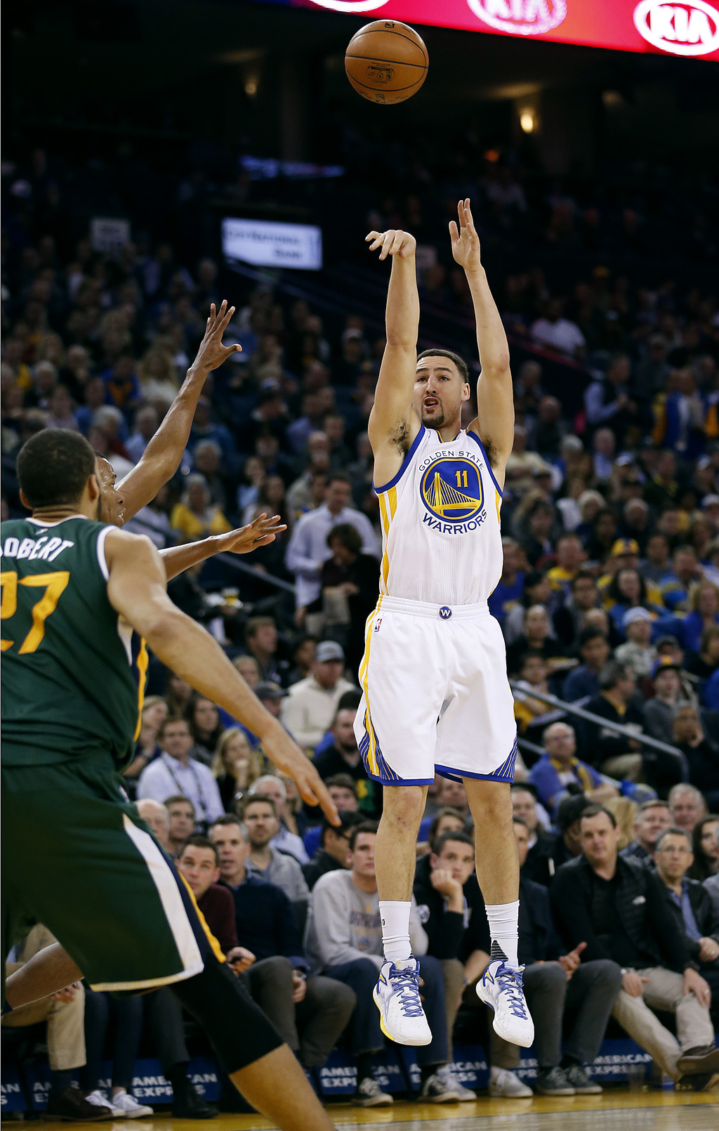 Golden State Warriors guard Klay Thompson (11) takes a 3-point shot over Utah Jazz center Rudy Gobert (27) during the first half of an ...