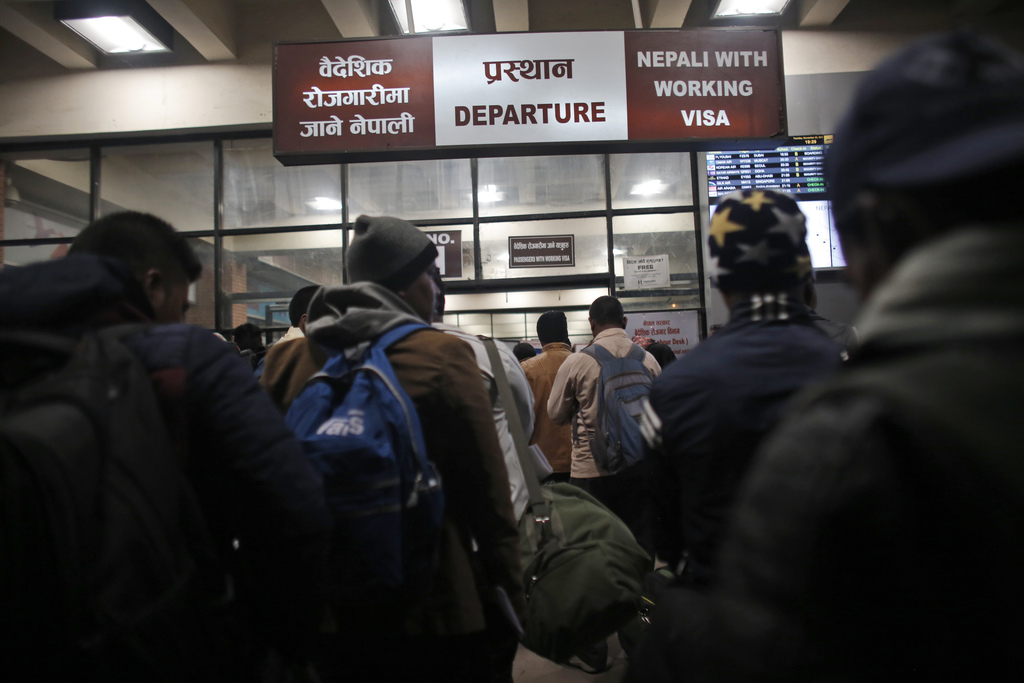In this Tuesday, Nov. 22, 2016 photo, Nepali workers stand in queues at the departure gate for migrant workers at Tribhuwan Internation...