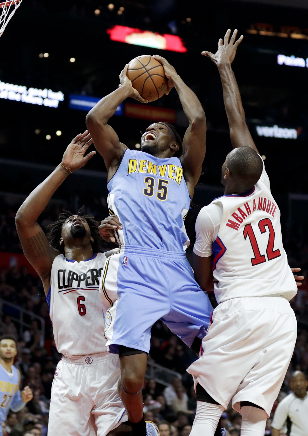 Denver Nuggets forward Kenneth Faried, middle, shoots between Los Angeles Clippers center DeAndre Jordan, left, and forward Luc Mbah a ...
