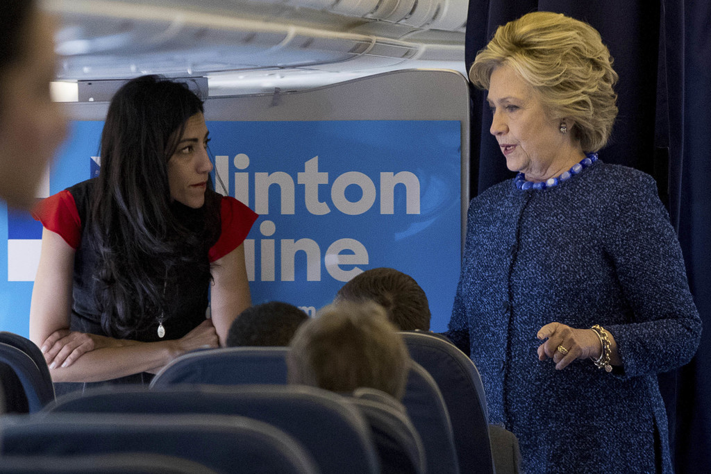 FILE - In this Oct. 28, 2016 file photo, Democratic presidential candidate Hillary Clinton speaks with senior aide Huma Abedin aboard h...