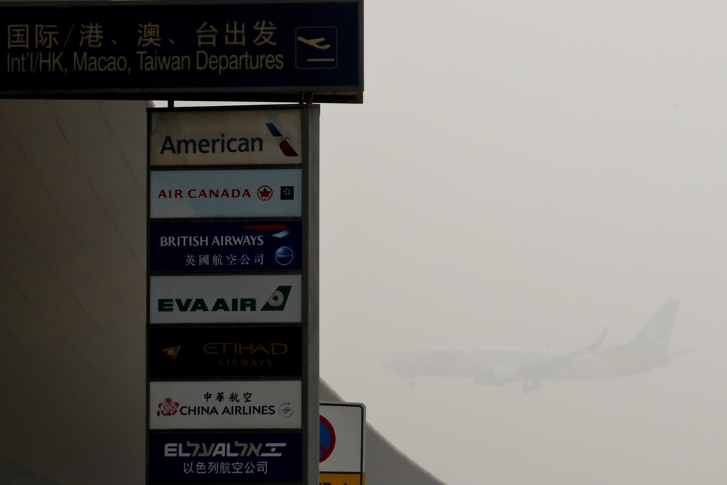 A passenger plane prepares to land at the Beijing Capital International Airport as the capital of China in heavy smog on Wednesday, Dec...