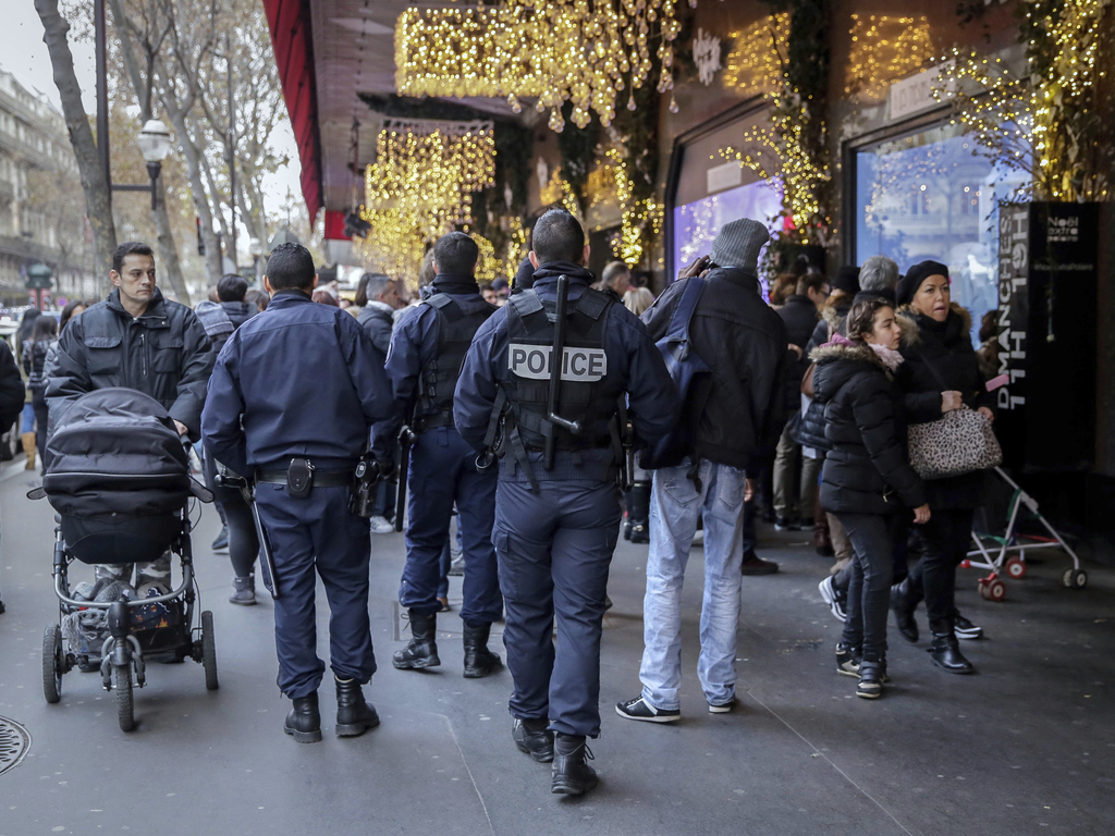 French police officers patrol outside the Galeries Lafayette department store in Paris, Tuesday, Dec. 20, 2016, the day after a truck r...