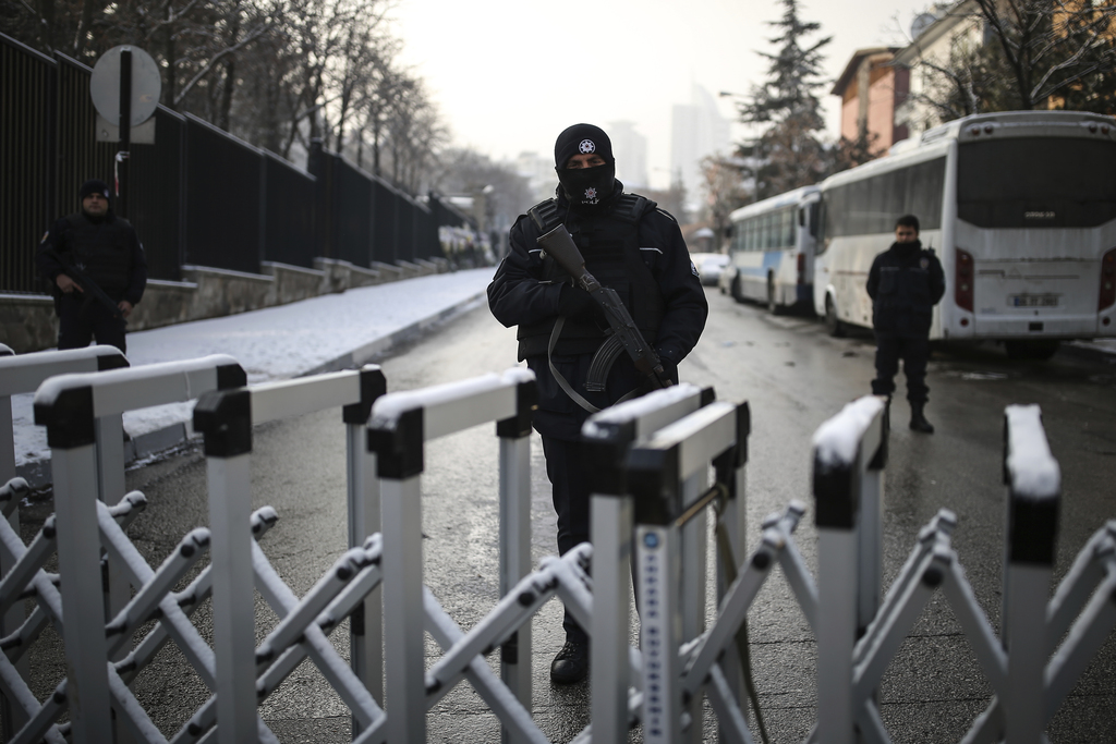 A Turkish police officer secures the road leading to the Russian embassy in Ankara, Turkey, Wednesday, Dec, 21, 2016. Russian Ambassado...