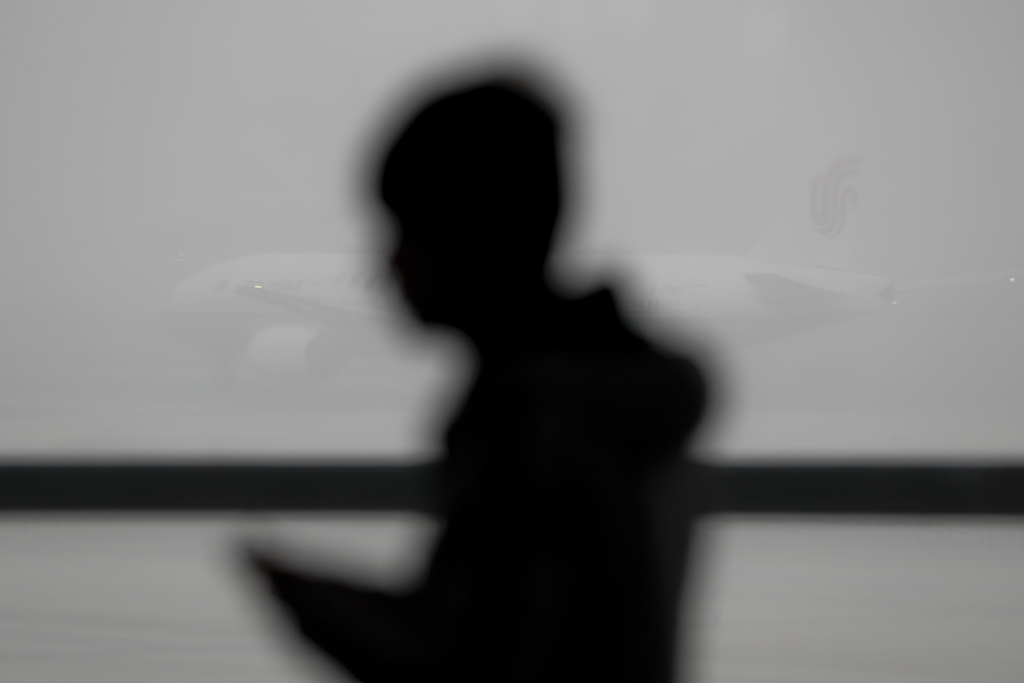 A man is silhouetted in front of an Air China passenger plane preparing to take off at the Beijing Capital International Airport as the...