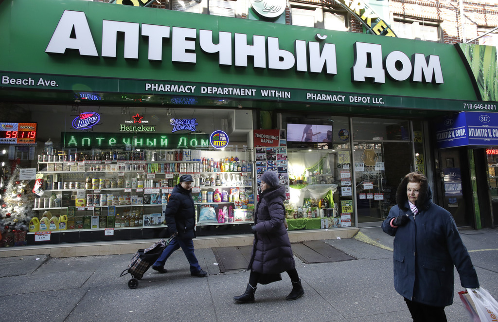 In this Dec. 16, 2016 photo, people walk past a Brighton Beach pharmacy that caters to the Russian community in the Brooklyn borough of...