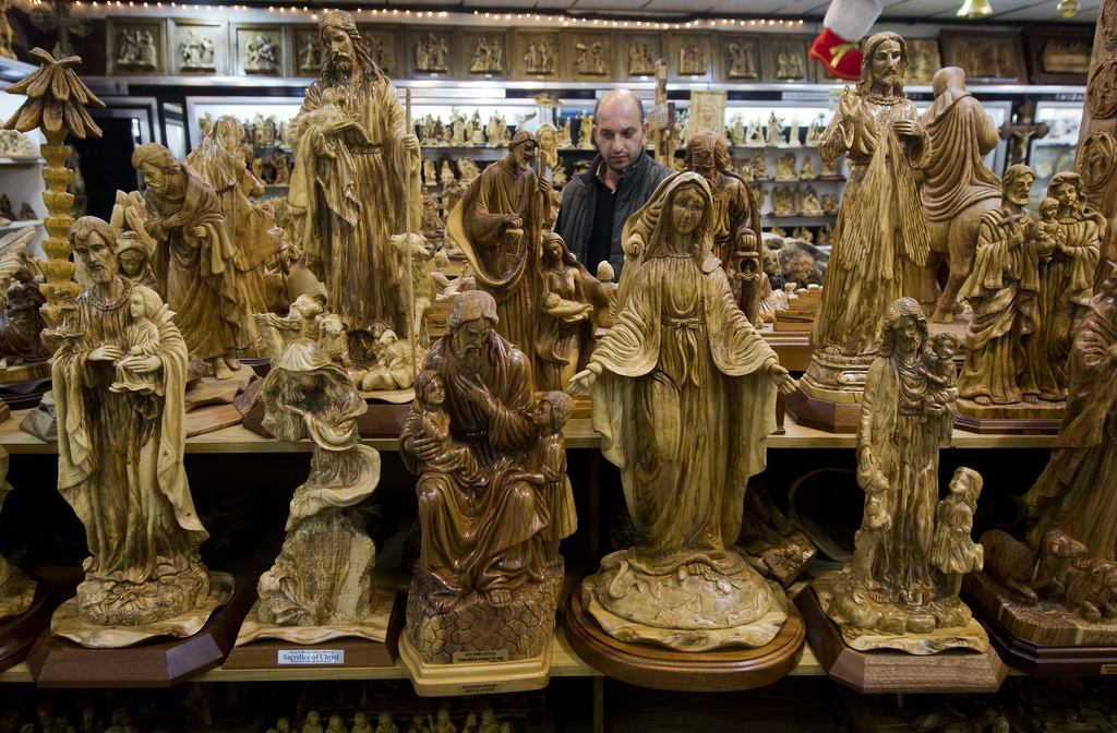 In this Monday, Dec. 12, 2016 photo, a shopkeeper walks through a souvenir shop in the West Bank city of Bethlehem. Christmas is approa...