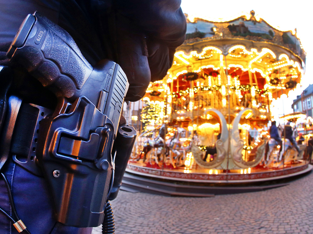 A German police officer stands next to a merry-go-round in the Christmas market in Frankfurt, Germany, Tuesday, Dec. 20, 2016 one day a...
