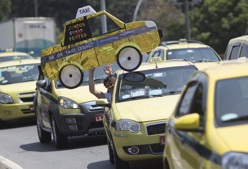 FILE - In this Nov. 11, 2015 file photo, a man holds up a mock cab as taxi drivers protest the Uber ride service in Rio de Janeiro, Bra...