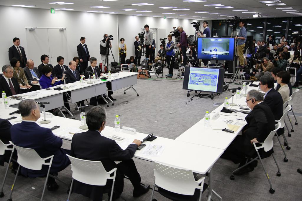 On the left side; Tokyo Gov. Yuriko Koike, center, speaks with Tokyo Olympics Organizing Committee President Yoshiro Mori, left, at the...