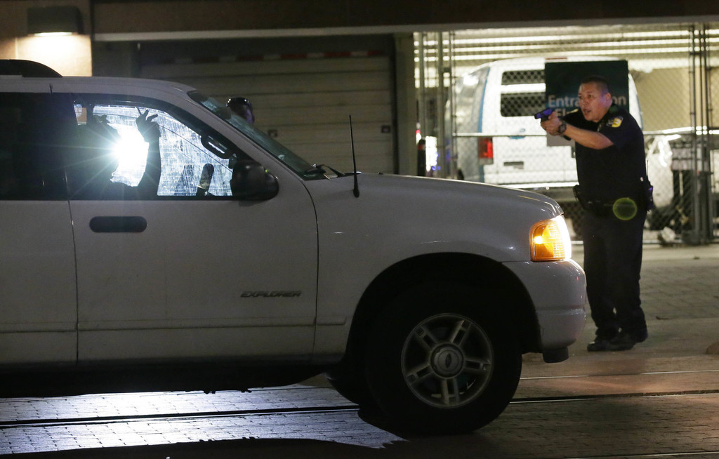 FILE - In this Thursday, July 7, 2016 file photo, a police officer stops a driver in downtown Dallas after police officers were shot an...