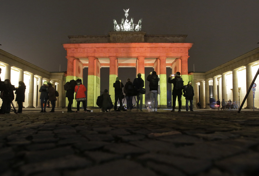 The Brandenburg Gate is illuminated in the colors of the German flag in Berlin, Germany, Tuesday, Dec. 20, 2016, the day after a truck ...