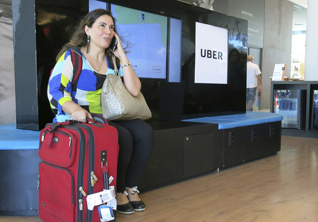In this Nov. 11, 2016 photo, Mirella Sanches, a 41-year-old architect, waits to be picked up at an Uber stand in Rio de Janeiro,Brazil....