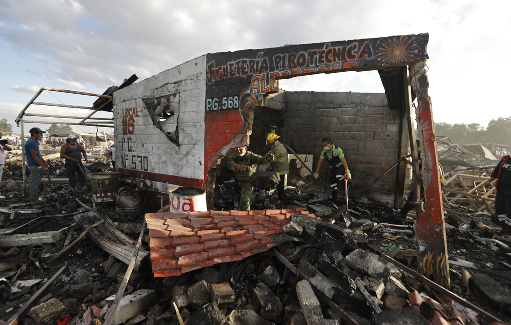 Firefighters and rescue workers remove debris from the scorched ground of Mexico's best-known fireworks market after an explosion explo...